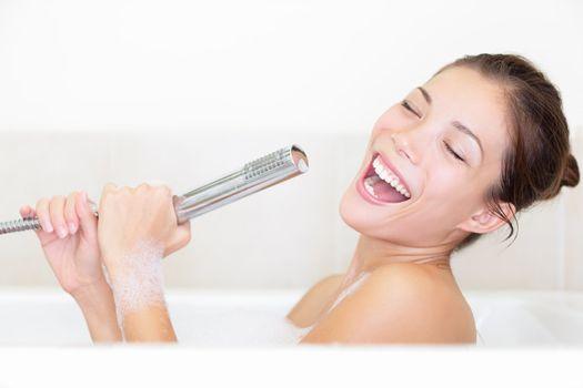 Bath woman singing in bathtub using shower head having fun. Funny photo of cute young mixed race woman.