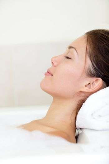 Spa woman relaxing in bath relaxed and serene with closed eyes. Pretty young mixed race Asian / Caucasian female model.