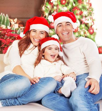 Picture of happy family sitting on sofa and wearing red Santa Claus hats, cheerful parents with daughter having fun at Christmas eve, little girl with mother and father celebrate New Year