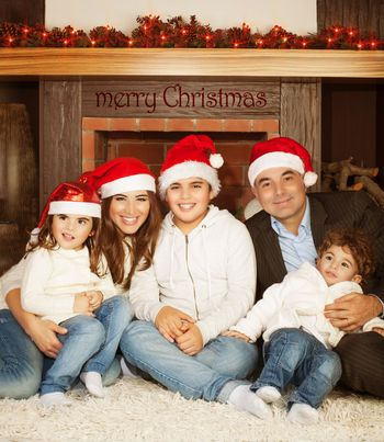 Photo of great happy family sitting near fireplace at home in Christmas eve, children with parents wearing red Santa Claus hat, enjoying winter holidays, New Year event, happiness and love concept