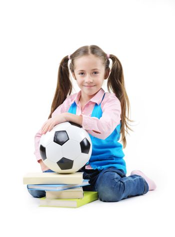 Cute little girl with books and soccer ball on white background