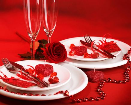 Photo of romantic dinner table setting, holiday banquet, white festive dinnerware on red tablecloth decorated with fresh rose flower and heart-shaped candles, Valentine day, two wineglasses