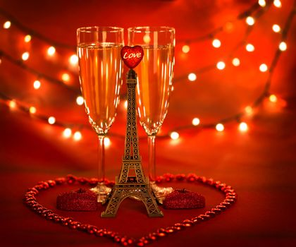Picture of two glass with champagne decorated with little Eiffel tower and heart-shaped candles and beads on red background with glowing lights, honeymoon in Paris, romantic holiday, Valentines day