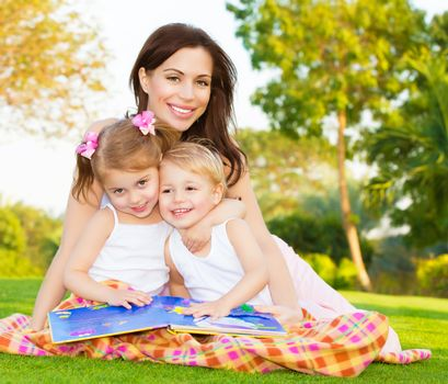 Picture of young happy family, beautiful mother with two cute kids having fun outdoors in spring, pretty female with son and daughter sitting down on green meadow on backyard, daycare concept