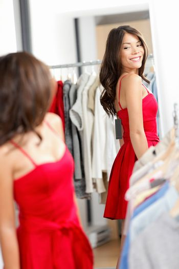 Woman shopping looking in mirror trying clothes dress in clothing store. Young beautiful multicultural woman trying on red dress in fitting room. Mixed race Caucasian Asian girl in her twenties.