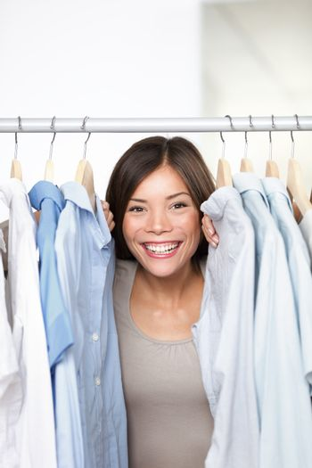 Small business clothing shop owner portrait in store. Funny image of woman clothes shop owner peeping through shirts smiling happy and excited at camera. Multicultural Asian Caucasian female model indoors.