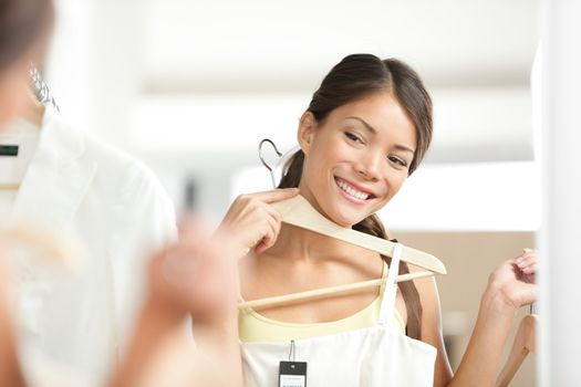 Girl Shopping clothing. Young woman shopper looking at dress in mirror smiling happy. Multiracial Asian / Caucasian female model inside clothes store.