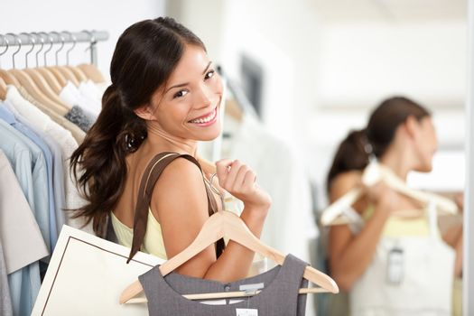 Happy shopping woman in clothing store smiling holding shopping bags and clothes dress. Beautiful Eurasian model inside
