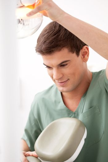 A young male dentist at work adjusting chair and light