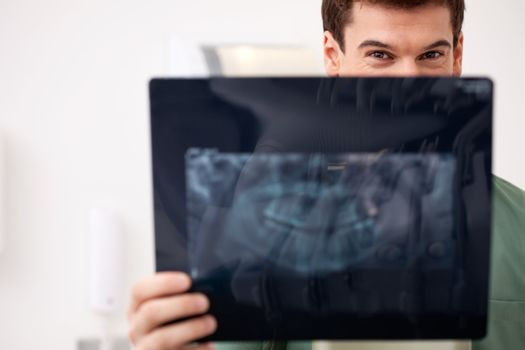 Young male dentist looking at an x-ray, eyes visiable over top
