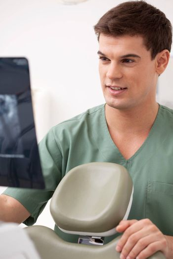 Young male dentist looking at an x-ray