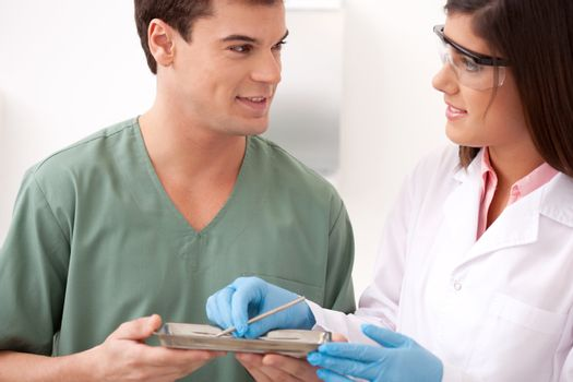 A male and female dentistry tream looking at eachother with a smile