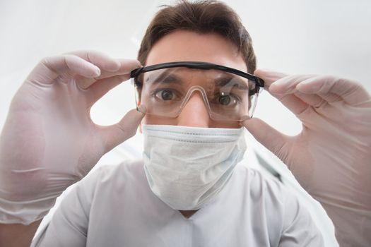 Close-up of young dentist adjusting his eyewear