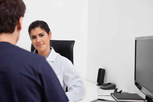 Female dentist sitting at her desk in front of patient at clinic