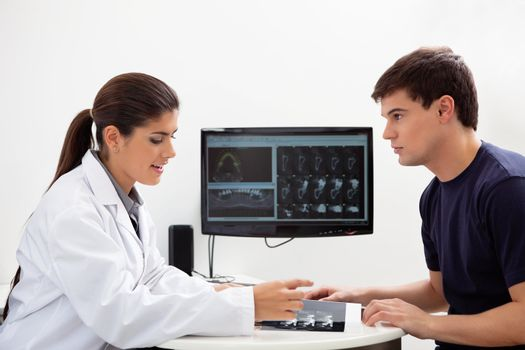 Female dentist discussing report with patient at clinic