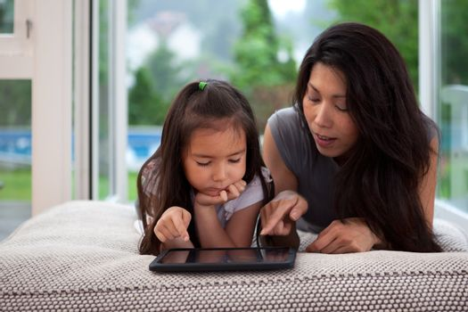 Mother and daughter laying on couch playing with a digital tablet