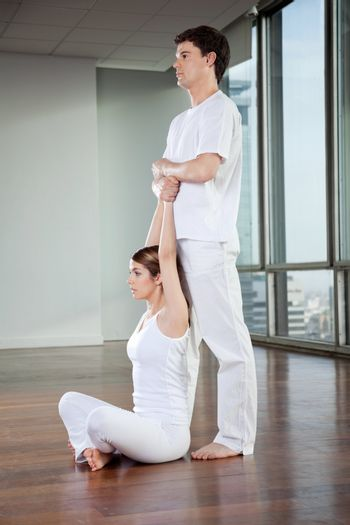 Yoga instructor teaching yoga positions to young woman at gym