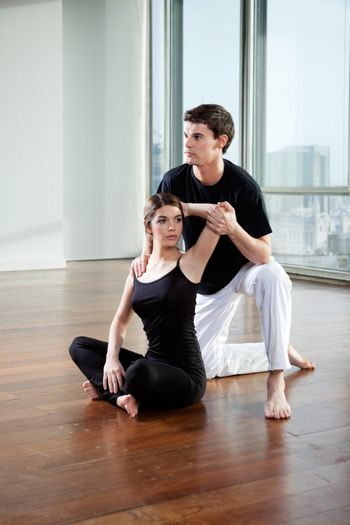 Yoga male instructor teaching yoga positions to young woman at gym