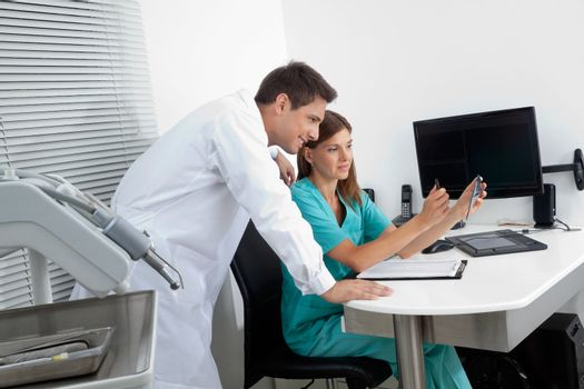Young male dentist with assistant analyzing report in clinic