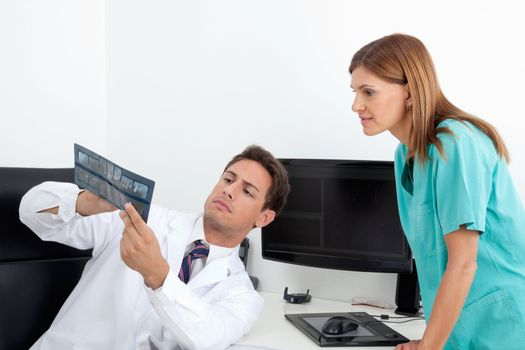Male dentist and female assistant analyzing X-ray report at office desk