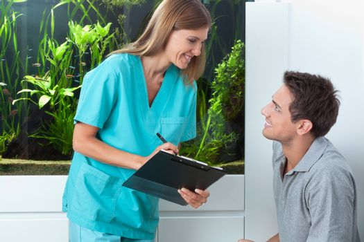 Happy female dentist with clipboard looking at male patient in clinic