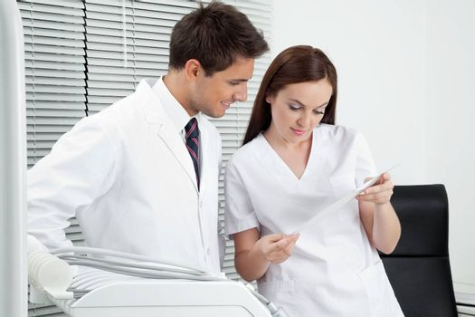 Male dentist with assistant discussing report in clinic