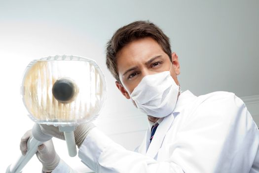 Portrait of young male dentist wearing surgical mask while holding dental lamp