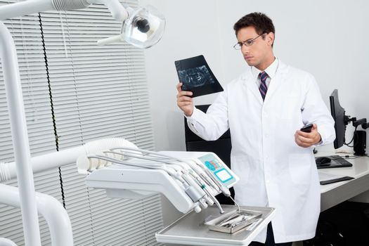 Male dentist analyzing patient's X-ray report in examination room