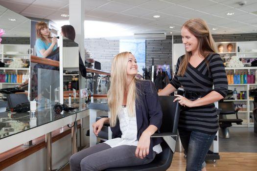 Hairdresser welcoming customer to beauty salon