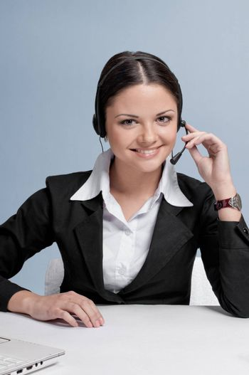 Busy business woman in office place talking by wireless headset over white table and laptop. Smile!