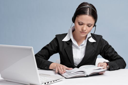 Busy business woman in office place talking by wireless headset over white table, laptop and diary. Tired.