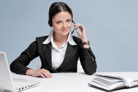 Busy business woman in office place talking by wireless headset over white table, laptop and diary