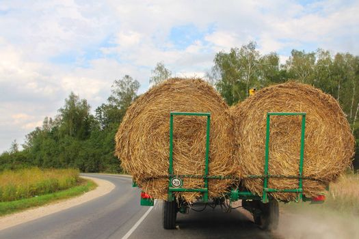 Transportation of haystacks after harvesting at sunny day
