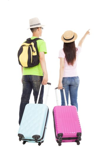 happy couple tourist with travel suitcase and pointing something