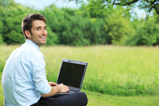 Young business man working on laptop outdoors