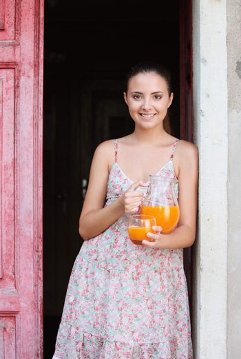 Young smiling woman with orange juice