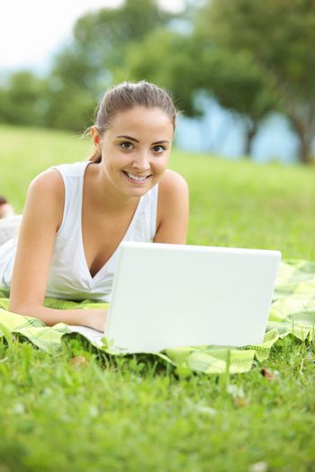 Cheerful girl working in laptop outdoors in a sunny day