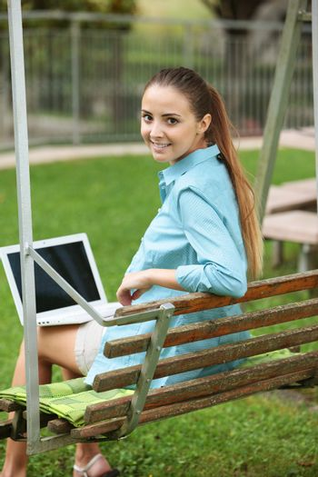 Cheerful girl working in laptop outdoors sitting on seesaw