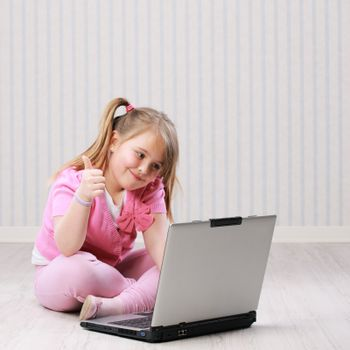Cute little girl working on a notebook computer showing thumbs up