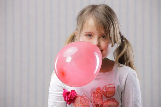 Portrait of a little beautiful girl with a pink balloon