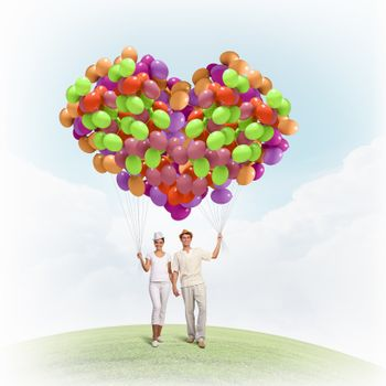 Image of young couple holding bunch of colorful balloons
