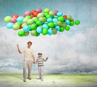 Image of father and son holding bunch of colorful balloons