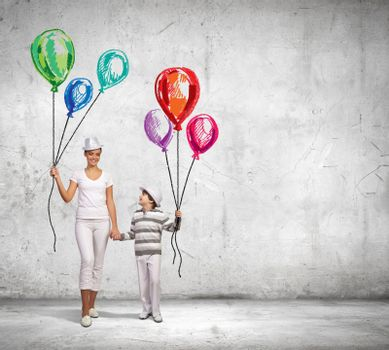 Image of mother and son holding bunch of colorful balloons
