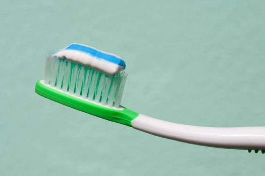 close up view of toothbrush and some toothpaste on it on green back