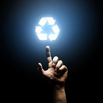 Human hand pointing with finger at recycle symbol