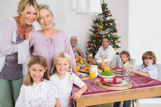 Three generations of women standing by the dinner table at christmas time