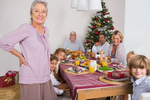 Smiling grandmother standing beside dinner table at christmas