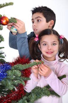 children decorating Christmas tree
