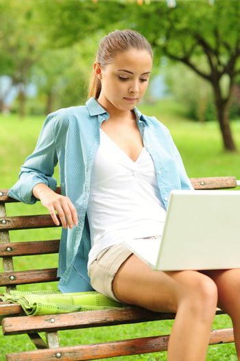 Beautiful girl working in laptop outdoors in a sunny day