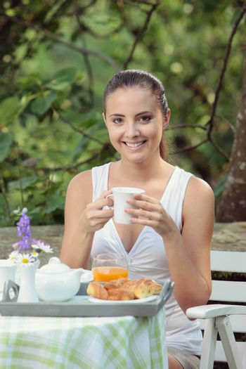 Young woman having breakfast in the garden on a summer day